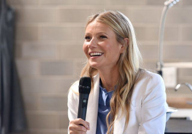 Gwyneth Paltrow smiles whilst holding a microphone. inch width=