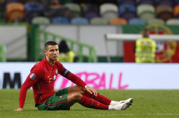 Portugal' s Cristiano Ronaldo, right, sits on the frequency during the international friendly football match